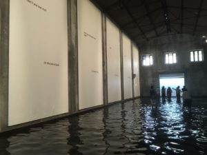 """Chilean Raul Zurita """"The Sea of Pain"""" (2016) demonstrated the versatile spaces available at venues like Aspinwall House. With the huge aircraft-hanger like space, a pool of salt water beckoned. You wade through to the end to read a poem about a dead Syrian child, the unphotographed brother of the iconic, immortalised portrait of Alan Kurdi. Words fail always."""