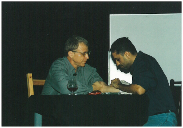 [names changed to protect the innocent] (1999) is a platform for original, exploratory and experimental work. Haresh Sharma is pictured drawing the blood of Ray Langenbach as part of his presentation, The Autologus Vampire. Image credit: The Necessary Stage